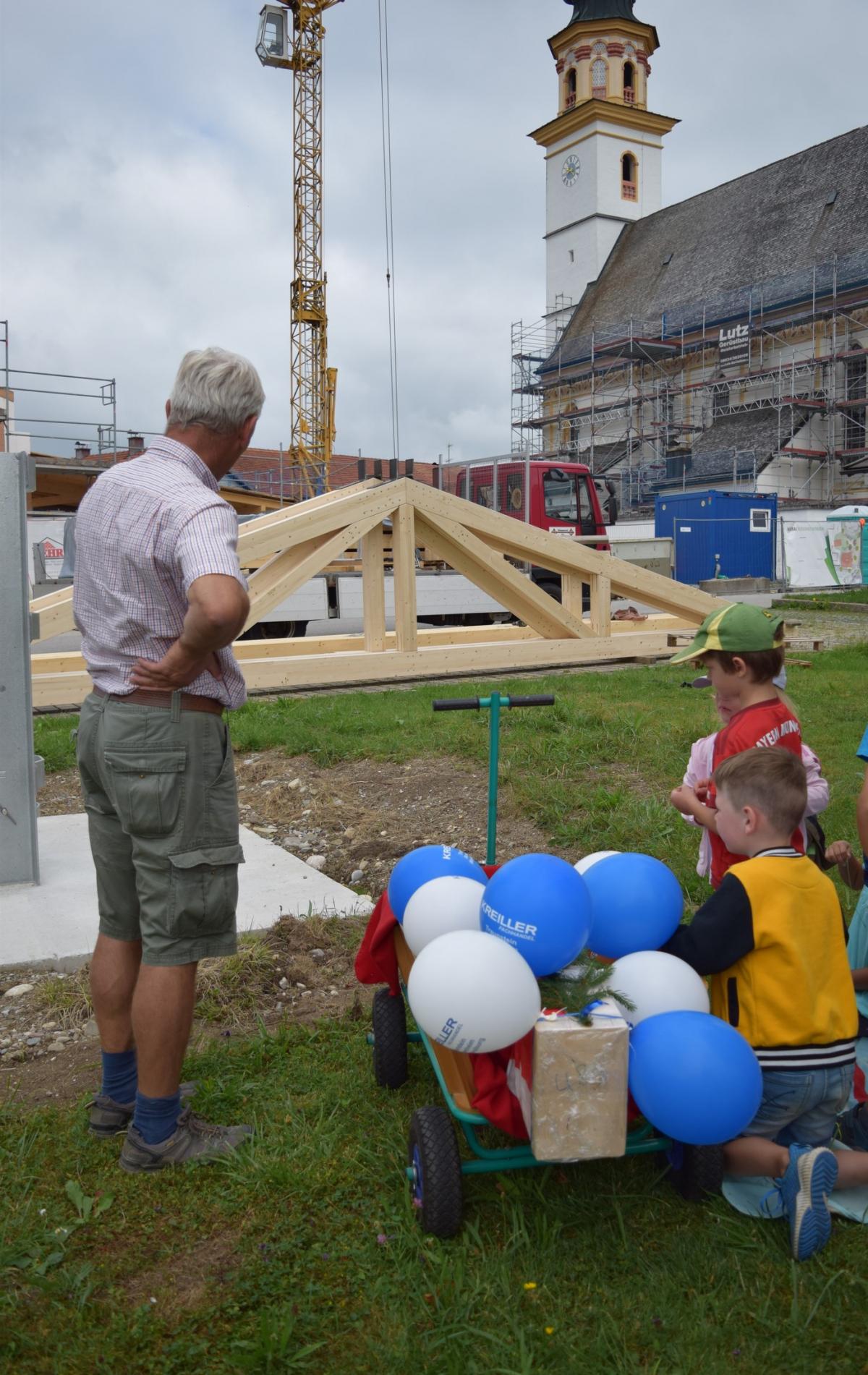 Noch liegt der stibitzte und mit Bändern und Luftballon geschmückte Firstaufdoppler auf dem Leiterwagen der Kindergarten-Knirpse. Bürgermeister Martin Fenninger erklärt ihnen, wozu das Holzteil notwendig ist.