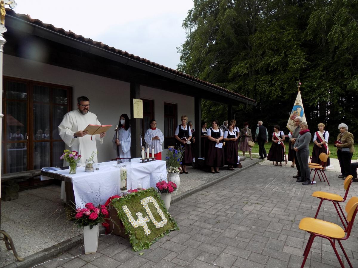 Gemeindereferent Martin Riedl hält den Gottesdienst zum 40. Jubiläum der Katholischen Frauengemeinschaft vor dem Freialtar, dessen floraler Schmuck an den Anlass erinnert.