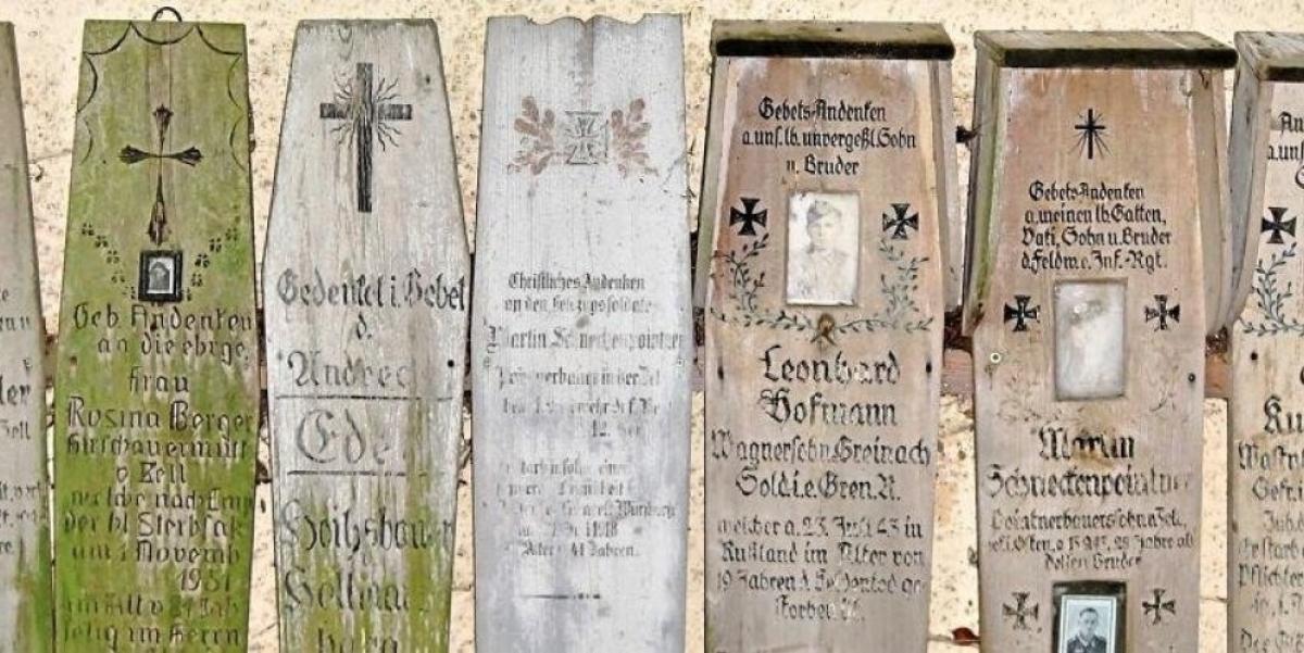 Verwitterte Totenbretter an der Rückseite der Kapelle erinnern zumeist an Bauerssöhne aus der Umgebung, die im Zweiten Weltkrieg gefallen sind.