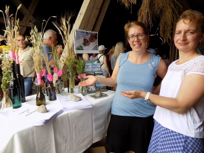 Die Mitarbeiterin der Ökomodellregion Waginger See – Rupertiwinkel, Jessica Romstötter, die die Veranstaltung moderierte, verweist zusammen mit (rechts) Maria Stadler auf die Urgetreide-Präsentation und das Infomaterial.