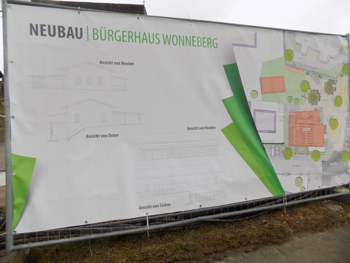 Das Plakat am Bauzaun, das die Pläne des Bürgerhauses zeigt.