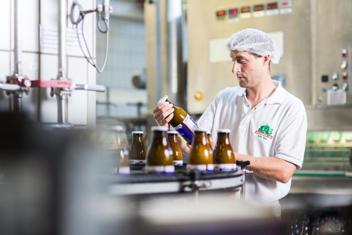 Die in der 1 Liter braunen Mehrwegflasche verpackte Biomilch kommt beim Kunden besonders gut an. Im Bild: Paul Althammer, stellv. Produktionsleiter bei der Fla-schenkontrolle