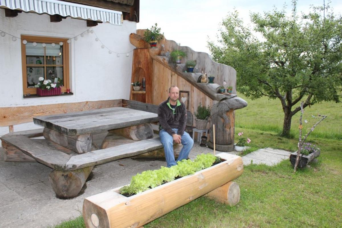Max Poschner jun. auf einer seiner vielen Hausbänke, umgeben von vielen Schnitzereien einschließlich der ausgehöhlten Stämme, die zu Hochbeeten geworden sind.