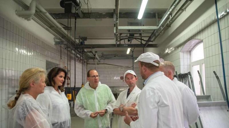 Ganz in weiß: Ministerin Michaela Kaniber (2. von links) lässt sich von Laufens Bürgermeister Hans Feil (Mitte) und den beteiligten Metzgern die Idee hinter dem städtischen Schlachthof erklären. Foto: Abgeordnetenbüro