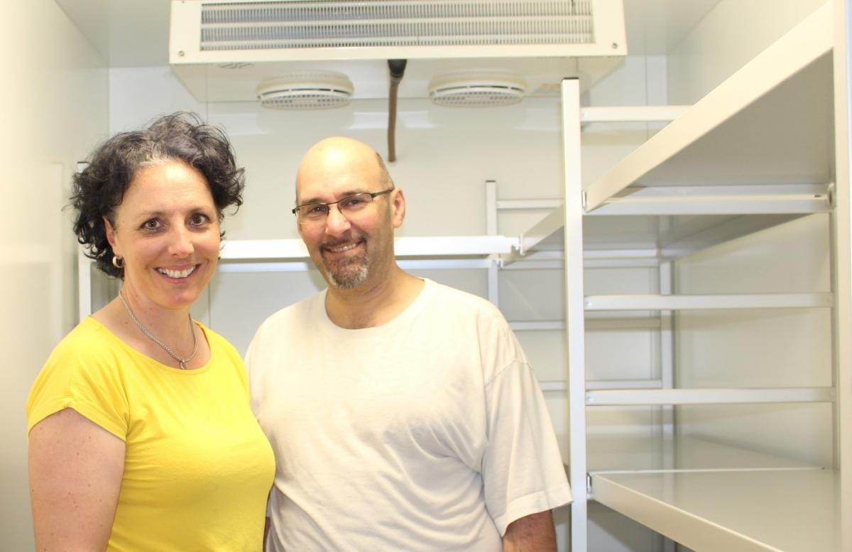 Barbara und Michael Wahlich vor ihrer neu eingebauten Kühlanlage. Dort können viel mehr Teiglinge als sonst reifen. Durch die spezielle Lagerung bei 3-4°C und hoher Luftfeuchtigkeit werden die enzymatischen Vorgänge verbessert, wodurch Brot und Gebäck besonders gut verträglich werden.